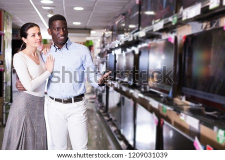 happy interracial couple choosing televisor in  household appliances store