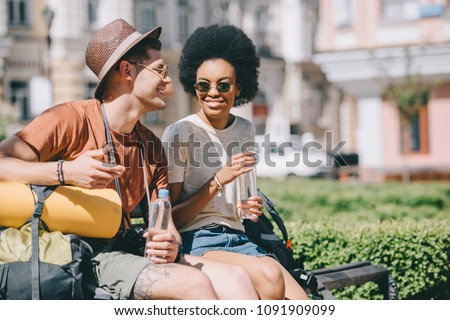 happy interracial couple of tourists with bottles of water sitting on bench