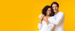 Happy interracial couple portrait. Joyful mixed-race sweethearts embracing and posing to camera, standing together on yellow background, panorama