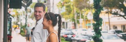 Happy interracial couple talking walking on city street shopping banner panorama. Young man and Asian woman looking at store window together, Naples, Florida, USA travel vacation panoramic.
