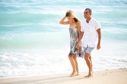 Happy Interracial Couple Walking on Sunny Beach