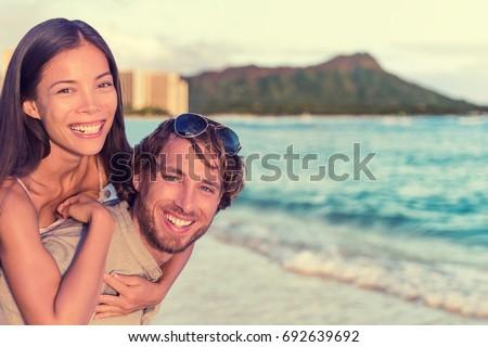 Happy interracial couple, woman piggybacking on man on Waikiki beach with Diamond Head Mountain landscape. Healthy people portrait, Honolulu, Hawaii. Travel holidays destination. #692639692