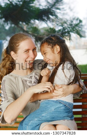 Happy interracial family. Mother and little daughter having fun in the park.