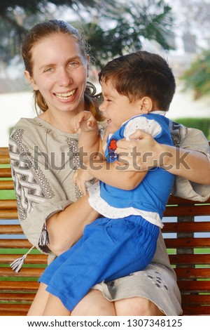 Happy interracial family. Mother and little son having fun in the park.