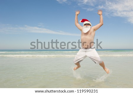 Happy joyful and cheerful Santa Claus on summer holiday, jumping in shallow water at tropical beach, isolated with ocean and blue sky as background and copy space.