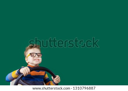 Happy joyful boy holding a steering wheel in his hands in the studio on a green background. Copy space. #1310796887