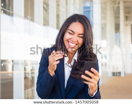 Happy joyful businesswoman getting funny message on phone outside. Beautiful young woman in office suit holding cellphone and laughing out loud. Joy concept