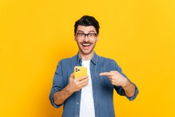 Happy joyful caucasian stylish guy with glasses, holding smartphone in hand and pointing at it finger, looking happily at camera with smiling, standing on isolated orange background