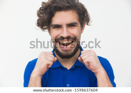 Happy joyful guy making joy gesture and laughing. Handsome bearded young man in blue casual t-shirt posing isolated over white background. Good news concept
