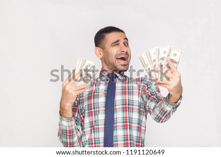 Happy joyful handsome young adult businessman in colorful checkered shirt with blue tie standing, holding fan of dollars and winking with open mouth. Indoor, studio shot, isolated on grey background #1191120649