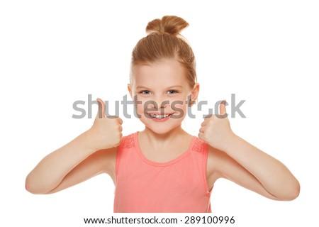 Happy joyful little girl smiling showing thumbs up, isolated on white background