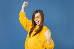 Happy joyful screaming young brunette woman 20s wearing yellow fur sweater eyeglasses posing clenching fists doing winner gesture keeping eyes closed isolated on blue color background studio portrait