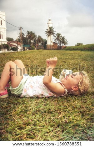 Happy joyful smiling child girl having fun lying on grass concept happiness joy childhood lifestyle