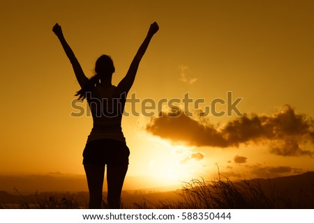 Happy joyful woman raising her arms up into the sky feeling happy and free.