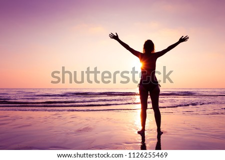 Happy joyful woman spreading hands on the beach at sunset, cheerful emotion and mindfulness, balance, mindful thinking #1126255469