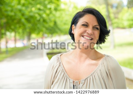 Happy joyful woman walking outdoors and having fun. Mature black haired lady looking away and laughing. Outdoor walk and joy concept #1422976889