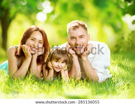 Happy joyful young family father mother and little daughter having fun outdoors playing together in summer park Mom Dad and kid laughing lyying on green grass enjoying nature outside Sunny day