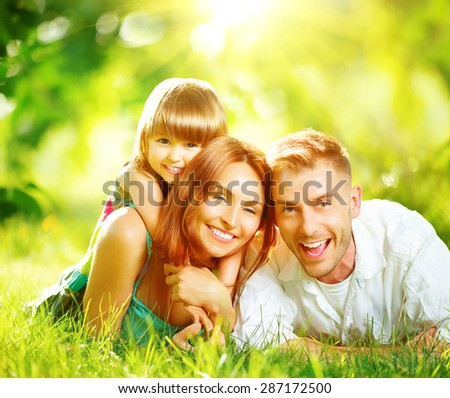 Happy joyful young family father, mother and little daughter having fun outdoors, playing together in summer park. Mom, Dad and kid laughing, lying on green grass, enjoying nature outside. Sunny day