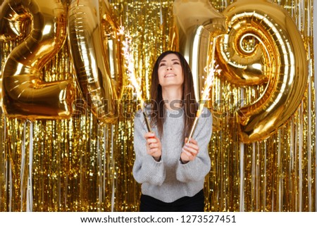 Happy joyful young woman happily holds in her hands fireworks on the background of balloons 2019 in the festive room. Cute girl celebrates the New Year. Magical celebration atmosphere.