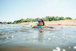 happy, joyful young woman in sunglasses swims on an inflatable circle in river on sunny summer day.. girl is enjoying summer vacation on shore of a lake or river. Active recreation. Dynamic image