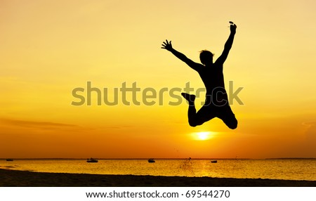 Happy jump during sunset or sunrise while on holiday at the beach.
