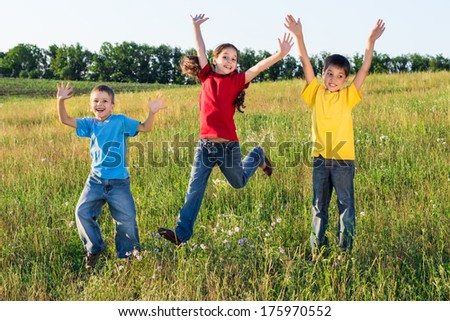 Happy jumping kids on green field, outdoors