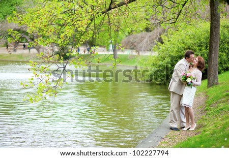 Happy just married couple hugging and kissing near the lake in park