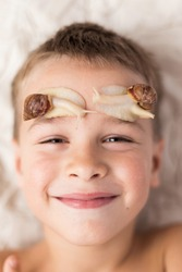 Happy kid boy playing with pet giant African snail (Achatina fulica). Snail crawling over face. Concept of not to be afraid of unusual animals. Selective focus