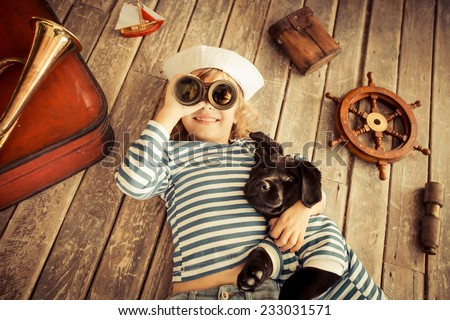 Happy kid dressed in sailor. Child playing with dog. Baby having fun at home. Travel and adventure concept. Unusual high angle view portrait