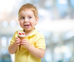 Happy kid eating icecream on blurred background