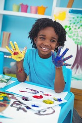 Happy kid enjoying painting with his hands at their desk