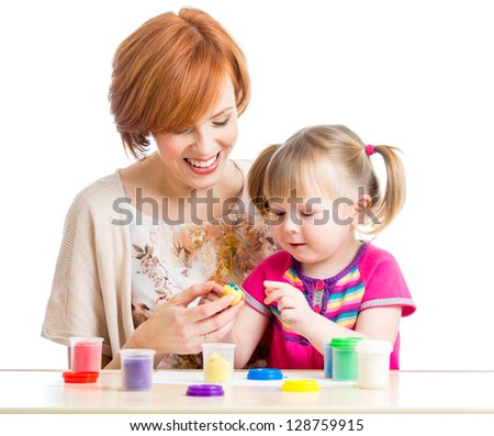 Happy kid girl and mother play colorful clay toy