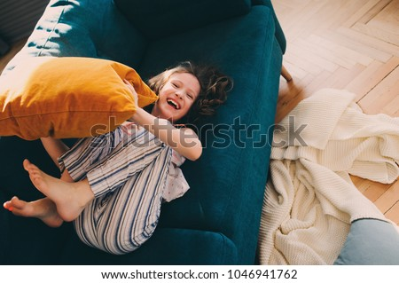 happy kid girl having fun at home in lazy weekend morning, fighting with pillows on cozy couch in pajamas