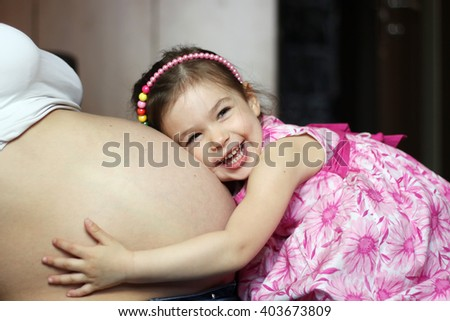 Happy kid girl hugging pregnant mother\'s belly, pregnancy and new life concept