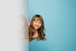 Happy kid, girl isolated on blue studio background. Looks happy, cheerful. Copyspace for ad. Childhood, education, emotions, business, facial expression concept. Peeking out from behind the wall