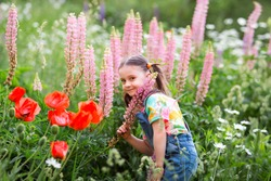 happy kid girl with ponytails in denim overalls with shorts and a multi-colored t-shirt sniffs pink lupine flowers.