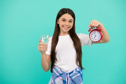 happy kid hold glass of water and alarm clock to stay hydrated and keep daily water balance in time, thirst.