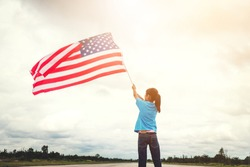 Happy kid little child standing with American flag USA celebrate 4th of July