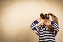 Happy kid looking ahead. Smiling child with spyglass. Travel and adventure concept. Freedom, vacation