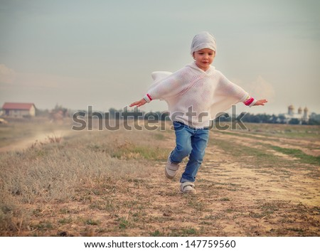 Happy kid playing airplanes with her arms open against blue summer sky background - stock photo
