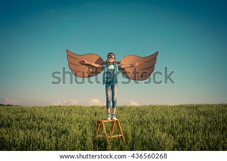 Happy kid playing. Child having fun outdoors. Kid with cardboard wings. Child in summer field. Travel and vacation concept. Imagination and freedom concept