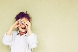Happy kid playing with binoculars. explore and adventure concept