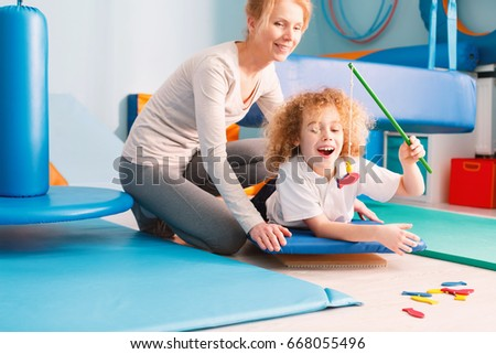 Happy kid playing with his sensory integration therapist #668055496