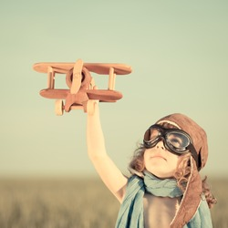Happy kid playing with toy airplane against blue summer sky background.