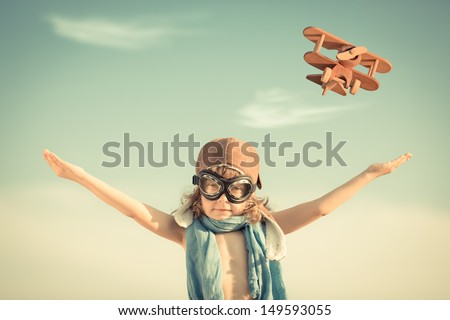 Happy kid playing with toy airplane against blue summer sky background. Vintage toned