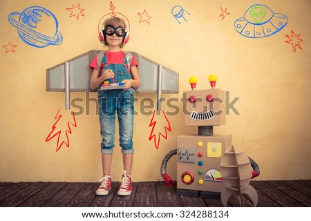 Shutterstock Happy kid playing with toy robot at home. Innovation technology and success concept