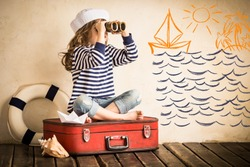 Happy kid playing with toy sailing boat indoors. Travel and adventure concept