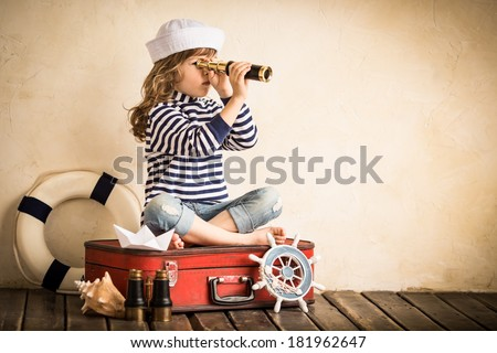 Happy kid playing with toy sailing boat indoors. Travel and adventure concept #181962647