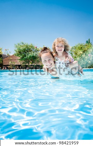 Happy kid playing with woman in swimming pool on a tropical resort at the sea. Summer vacations
