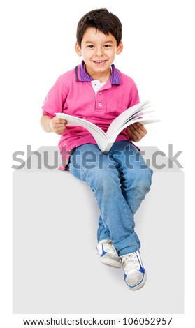 Happy kid reading a book and smiling - isolated over white background